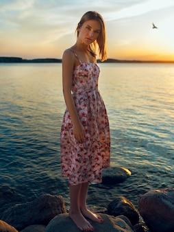 Молодая и симпатичная блондинка стоит на берегу в платье и любуется закатом