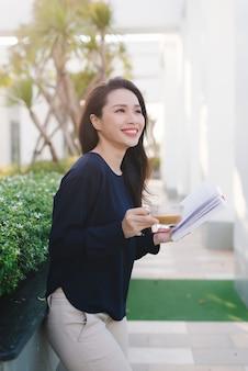 화창한 날에 공원에서 책을 읽고 젊고 예쁜 여자.
