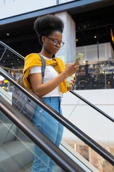 Молодая и симпатичная женщина из поколения миллениума на эскалаторе в торговом центре