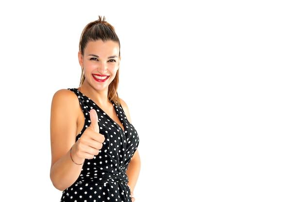 Молодая и симпатичная улыбающаяся женщина смотрит прямо перед собой и делает знак одобрения, поднимая большой палец правой руки.