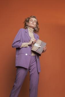 若くてきれいな女性がオレンジ色の背景に彼女の手でスタイリッシュなバッグと紫のスーツでポーズします。