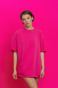 ピンクの背景にポーズをとってマゼンタのtシャツを着て若くてきれいな女性