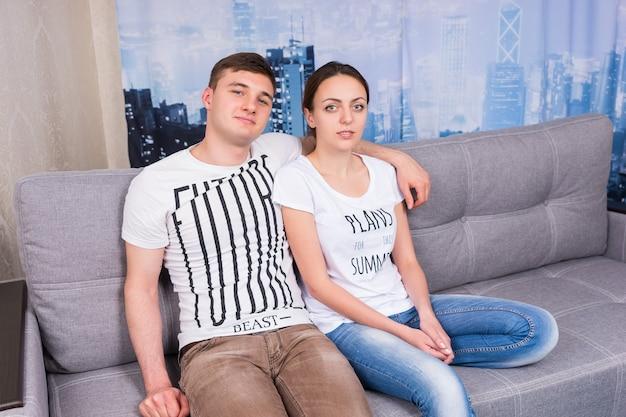 リラックスした雰囲気の中で一緒に自宅でソファに抱きしめて座っている若くてロマンチックなカップル
