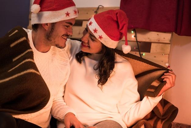 겨울 옷과 크리스마스 모자를 쓰고 젊고 낭만적 인 커플