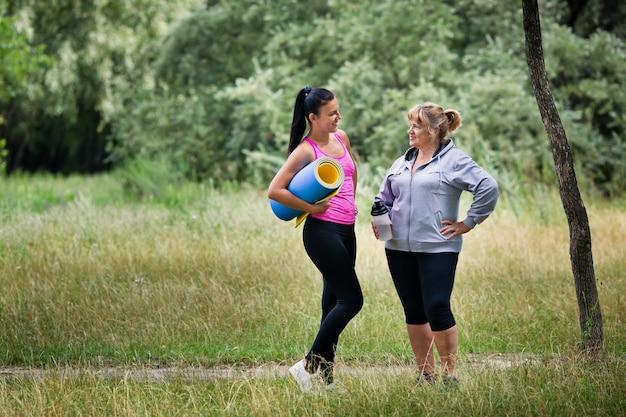 制服を着た若いとシニアの運動女性は公園で話しています。
