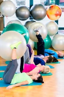 Молодые и пожилые люди, тренирующиеся с мячом в тренажерном зале