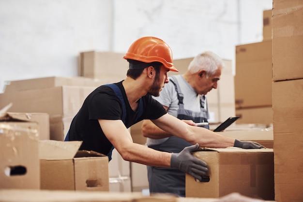 制服を着た若いストレージワーカーとシニアストレージワーカーが倉庫で一緒に働いています。