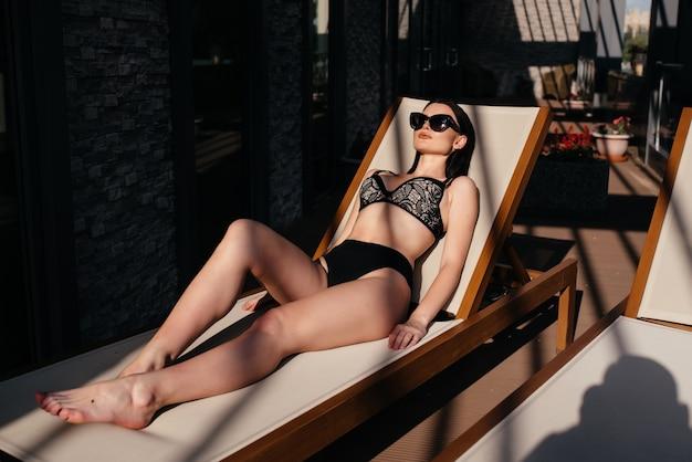 熱帯のビーチで晴れた日を楽しんでいる若くて官能的な女性