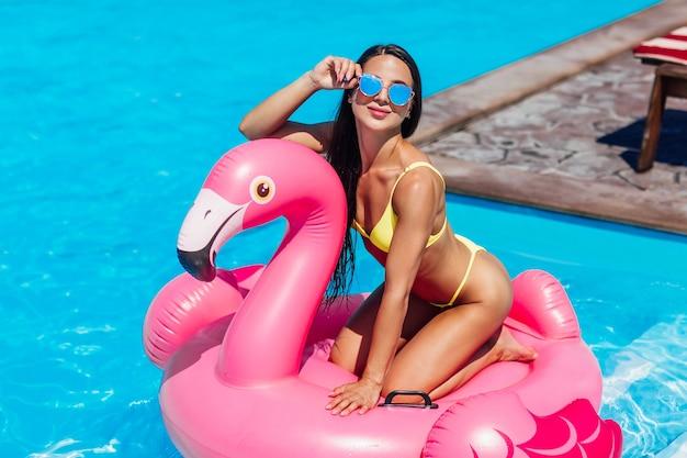 젊고 섹시한 소녀는 여름에 수영복과 선글라스를 끼고 부풀릴 수 있는 분홍색 플라밍고를 타고 수영장에서 즐겁게 웃고 웃고 있습니다.