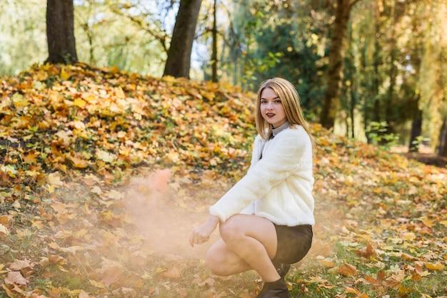 秋の公園でポーズをとって黒のドレスと毛皮のジャケットを着て若くてスリムな女性
