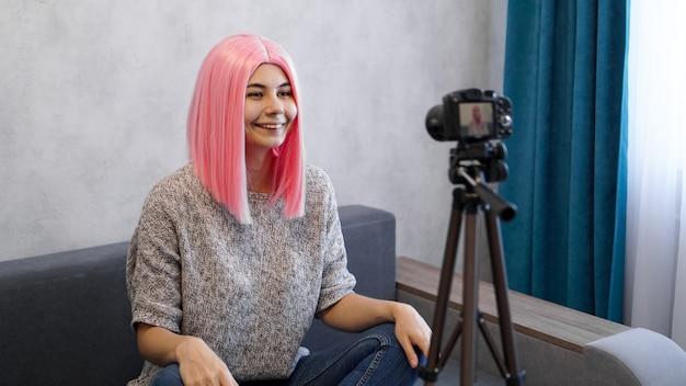 Молодой и умный. красивая молодая женщина с розовыми волосами в повседневной одежде во время записи видео blod