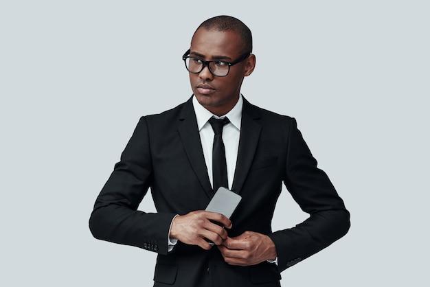 젊고 똑똑합니다. 회색 배경에 서 있는 동안 스마트 폰을 사용하여 정장을 입은 매력적인 젊은 아프리카 남자