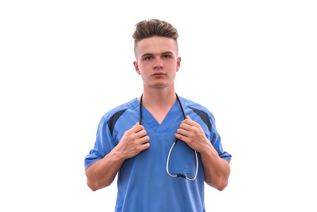 白い壁に隔離された聴診器のポーズで医療制服を着た若くて賢い医者