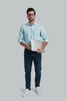 若くて賢い。ラップトップを携帯し、灰色の背景に立ってカメラを見ている若い男の全長