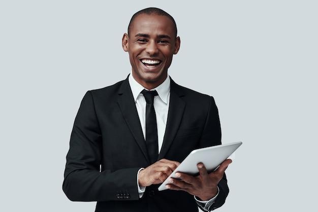 젊고 똑똑합니다. 회색 배경에 서서 카메라를 보고 웃고 있는 정장 차림의 젊은 아프리카 남자