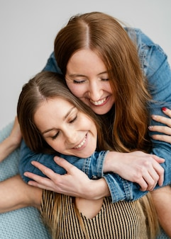 포옹하는 젊고 웃는 여자 친구