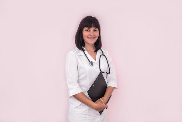 ピンクで分離されたクリップボードを持つ若くて笑顔の医者