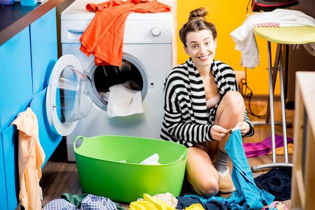 Молодая и улыбающаяся домохозяйка сидит у стиральной машины с яркой одеждой дома