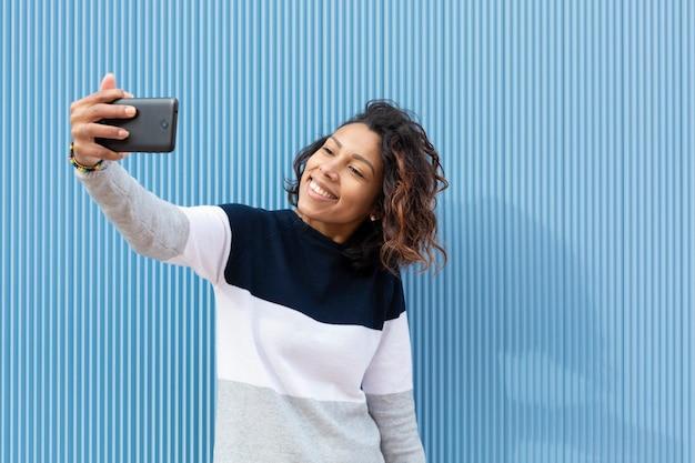 青い壁に彼女の携帯電話で肖像画を撮る若くて笑顔のティーンエイジャーの女の子