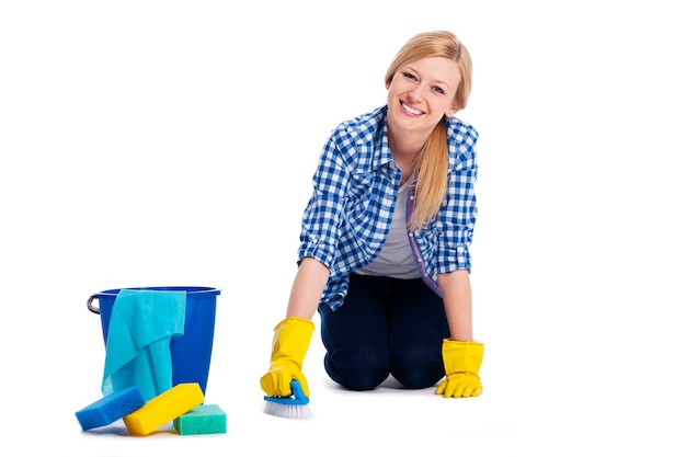 젊고 웃는 여자는 바닥을 청소