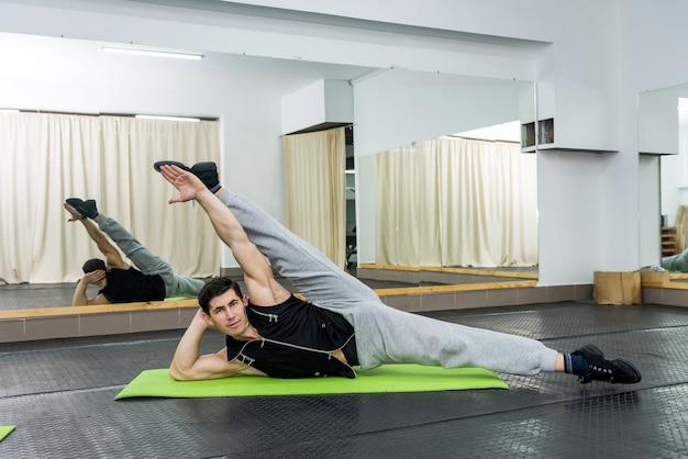 ジムでストレッチ体操をする若くてスポーティーな男