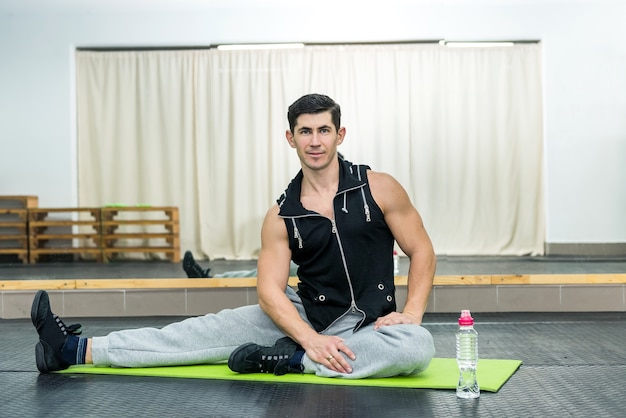 젊고 낚시를 좋아하는 사람이 체육관에서 스트레칭 운동을