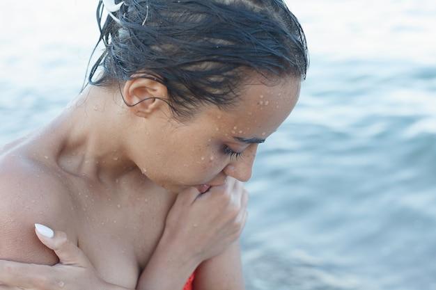 Молодая и спортивная девушка позирует на пляже летом.