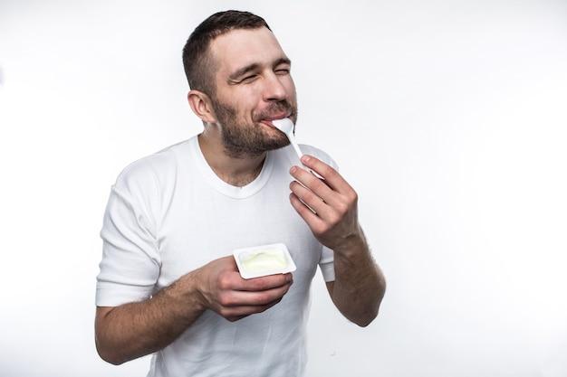 젊고 강한 남자가 요구르트를 먹고 있습니다. 그는 기쁨으로 그 일을 하고 있습니다. 흰색 배경에 고립