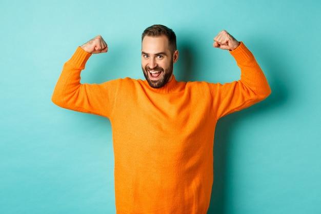 Молодой и сильный мужчина выглядит уверенно, сгибает бицепсы и демонстрирует силу мышц, уверенно улыбается и стоит на голубом фоне.