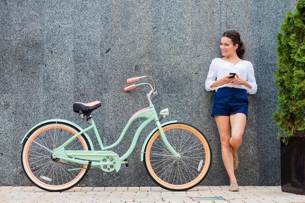 젊고 세련된. 거리에서 그녀의 빈티지 자전거 근처에 서 있는 아름 다운 젊은 웃는 여자