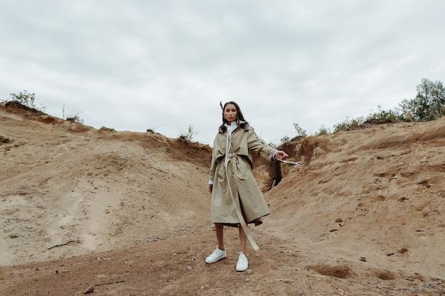 砂場のベージュのトレンチコートでダイナミックにポーズをとる若くてスタイリッシュなブルネットの女の子。