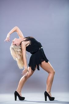 회색 배경에 포즈 젊고 세련된 댄서