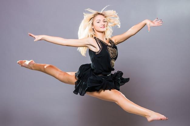 Молодой и стильный танцор позирует на сером фоне