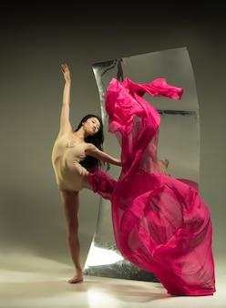 鏡付きの茶色の壁に若くてスタイリッシュなモダンなバレエダンサー。表面での錯覚の反射。柔軟性の魔法、生地による動き。クリエイティブアートダンス、アクション、インスピレーションのコンセプト。