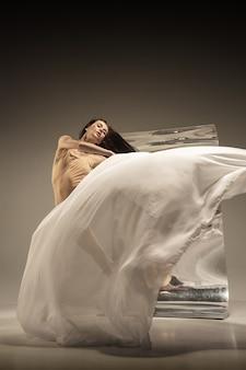 Молодая, стильная современная балерина на коричневой стене с зеркалом