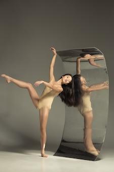 ミラー付きブラウンの若くてスタイリッシュなモダンなバレエダンサー