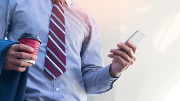 ヤングで成功したビジネスマンは彼のスマートフォンでメッセージを読んでいます。