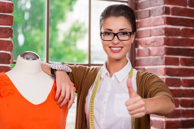 Молодой и успешный модельер. красивая молодая женщина-модельер, опираясь на манекен и показывая большой палец вверх, стоя перед окном
