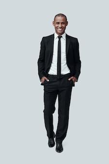 젊고 성공적입니다. 회색 배경에 서서 카메라를 보고 웃고 있는 정장 차림의 잘생긴 젊은 아프리카 남자의 전체 길이