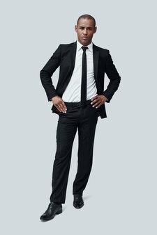 젊고 성공적입니다. 회색 배경에 서서 카메라를 바라보는 정장 차림의 잘생긴 젊은 아프리카 남자의 전체 길이