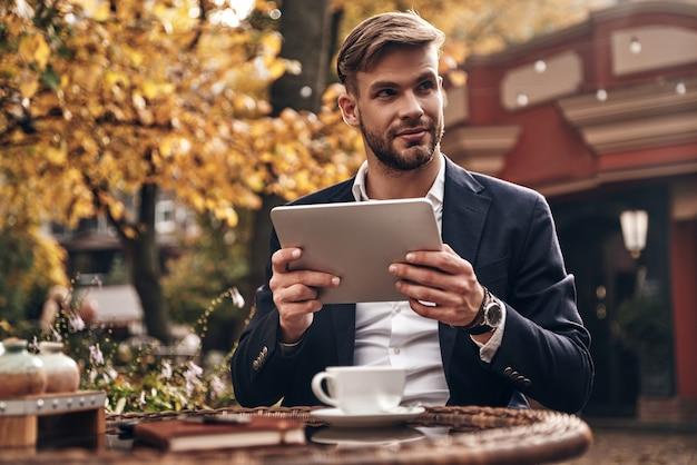 Молодой и успешный. красивый молодой человек в элегантной повседневной одежде, используя цифровой планшет и глядя в сторону с улыбкой, сидя в ресторане на открытом воздухе