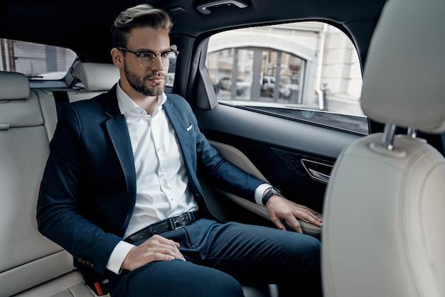 젊고 성공적입니다. 차에 앉아있는 동안 멀리보고 전체 양복에 잘 생긴 젊은 남자