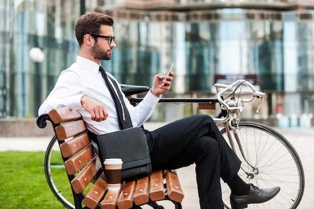 젊고 성공적입니다. 사무실 건물을 배경으로 자전거 근처 벤치에 앉아 휴대전화를 들고 있는 잘생긴 젊은 사업가의 측면