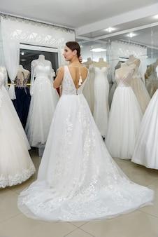 サロンでウェディングドレスを着た若くて小さな花嫁