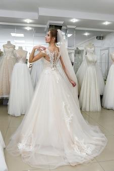 Молодая и крошечная невеста в свадебном платье в салоне