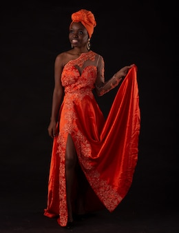 Young angolan girl wearing dress and turban studio photo on a black background