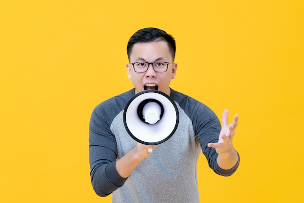 Young angry asian man shouting into megaphone