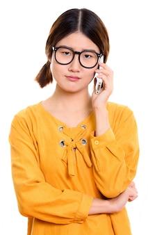 Молодая злая азиатская женщина разговаривает по мобильному телефону