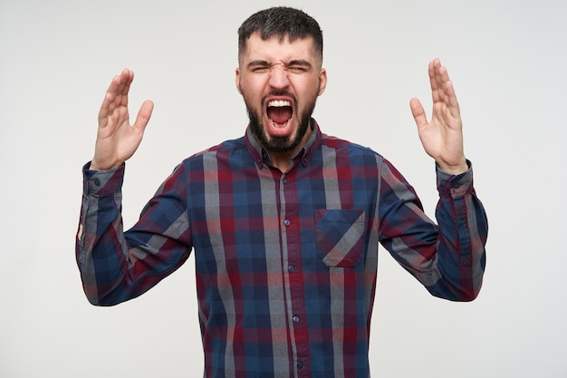 Young angry brunette man with beard raising emotionally his hands and screaming violently with closed eyes, isolated over white wall