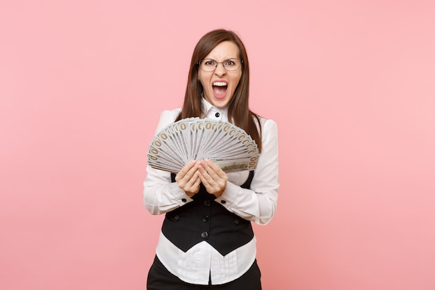 Young angry business woman in glasses holding bundle lots of dollars, cash money and screaming isolated on pink background. lady boss. achievement career wealth concept. copy space for advertisement.